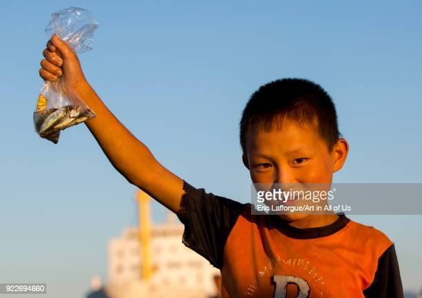 North Korean child boy showing fishes in a plastic bag he catched Kangwon Province Wonsan North Korea on September 10 2012 in Wonsan North Korea