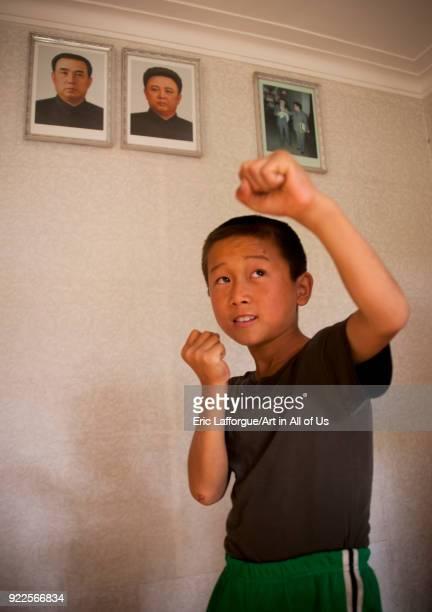 North Korean child doing taekwondo under the portraits of Kim il Sung and Kim Jong il South Pyongan Province Chonsam Cooperative Farm North Korea on...