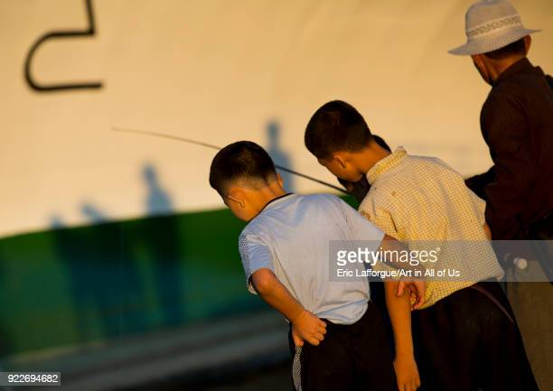 North Korean children fishing in the sea in front of a ship Kangwon Province Wonsan North Korea on September 10 2012 in Wonsan North Korea
