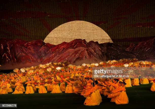 North Korean dancers in front of rising sun over mount Paektu made by children holding up boards during Arirang mass games in may day stadium Pyongan...