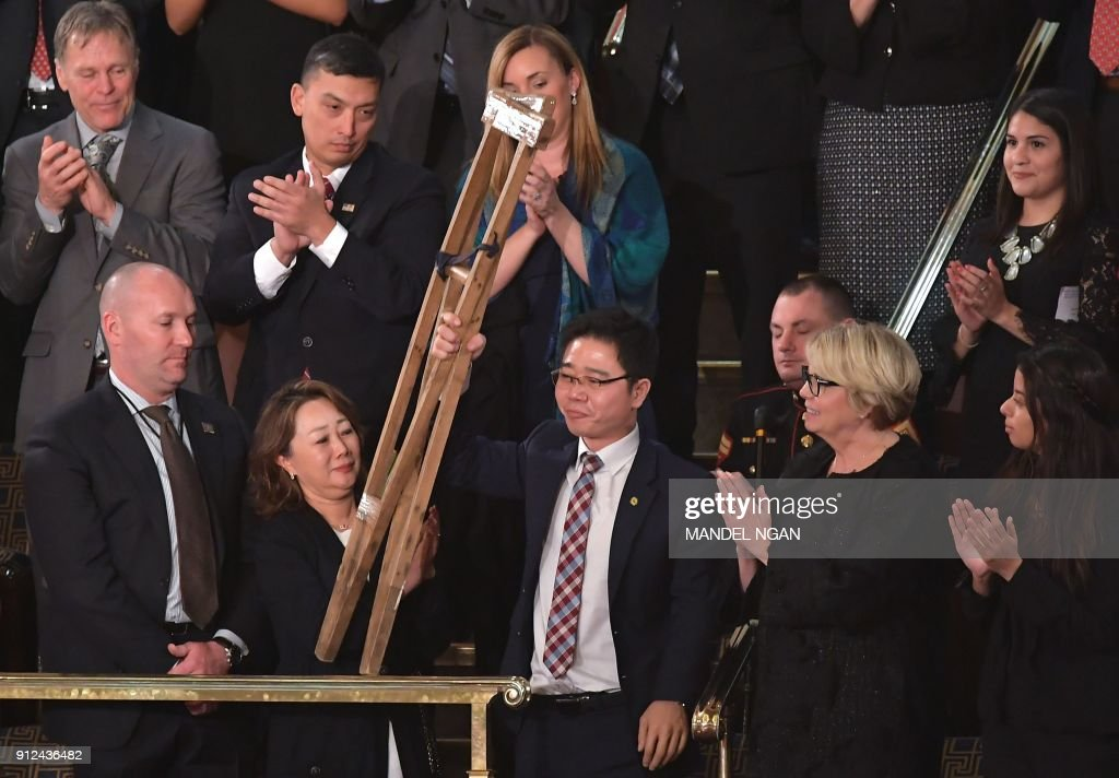 TOPSHOT - North Korean defector Ji Seong-ho raises his crutches as he is recognized by US President Donald Trump during the State of the Union address at the US Capitol in Washington, DC, on January 30, 2018. / AFP PHOTO / Mandel NGAN