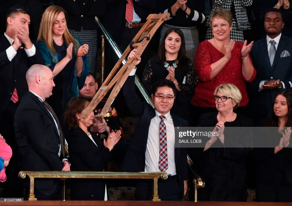 North Korean defector Ji Seong-ho raises his crutches as US President Donald Trump delivers the State of the Union address at the US Capitol in Washington, DC, on January 30, 2018. LOEB