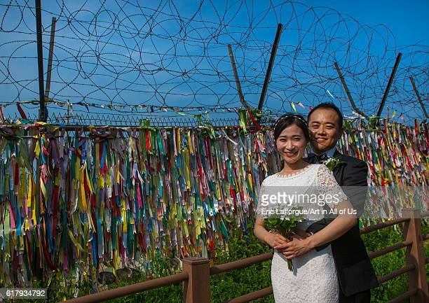 North korean defector joseph park with his south korean fiancee juyeon in front of messages of peace written on ribbons left on dmz sudogwon paju...