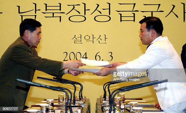 North Korean delegation leader Army Major General An Iksan exchanges an agreement with his South Korean counterpart Rear Admiral Park Junghwa during...