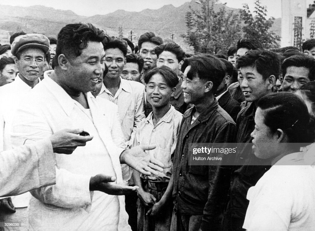 North Korean dictator, Kim Il Sung (1912 - ), chats with workers on an unofficial visit to the Hichun Machine Plant.