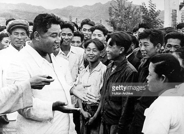 North Korean dictator, Kim Il Sung , chats with workers on an unofficial visit to the Hichun Machine Plant.