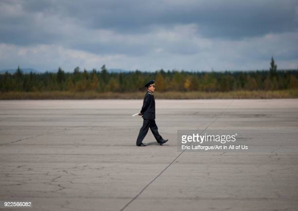 North Korean employee walking on runway Samjiyon airport Ryanggang Province Samjiyon North Korea on September 18 2011 in Samjiyon North Korea