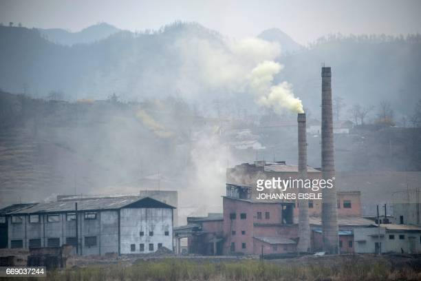 A North Korean factory billows smoke near the Yalu river near Sinuiju opposite the Chinese border city of Dandong on April 16 2017 Dandong city is...