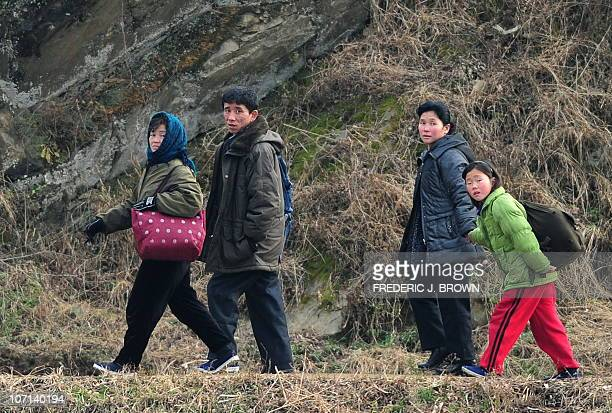 A North Korean family walks near the shoreline of the Yalu River some 70 kms north of Dandong in northeast China's Liaoning province which lies...