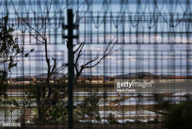 A North Korean farmer is seen through a razor wire fence near the border city of Dandong Liaoning province northern China across from the city of...