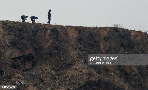 North Korean farmers plant near the Yalu river near Sinuiju opposite the Chinese border city of Dandong on April 16 2017 Dandong city is the main...