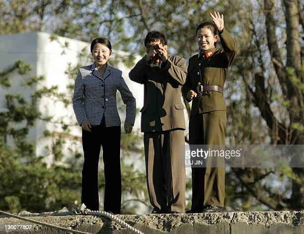 A North Korean female soldier waves whilst a man looks through binoculars and another woman stands nearby on the bank of Yalu River in the North...