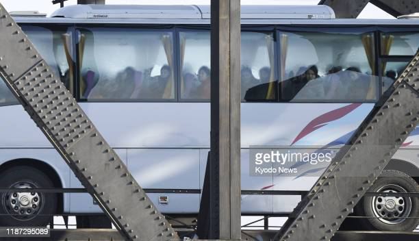 North Korean female workers look out of the window as the bus carrying them crosses the Sino-Korean Friendship Bridge from North Korea's Sinuiju to...