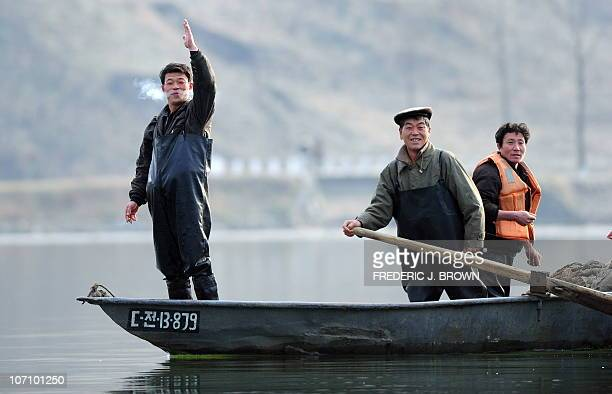 A North Korean fisherman gestures from his boat on the Yalu River some 70 kms north of Dandong in northeast China's Liaoning province which lies...
