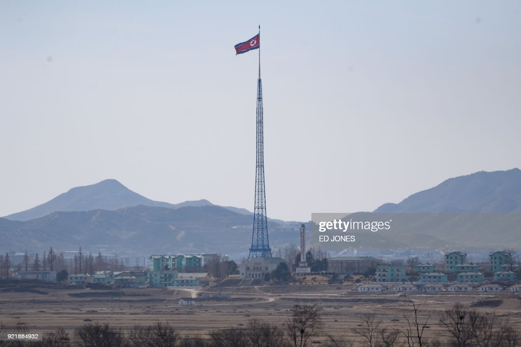 A North Korean flag flies above a village near the truce village of Panmunjom, seen from within the Demilitarized Zone (DMZ) separating North and South Korea on February 21, 2018. / AFP PHOTO / Ed JONES