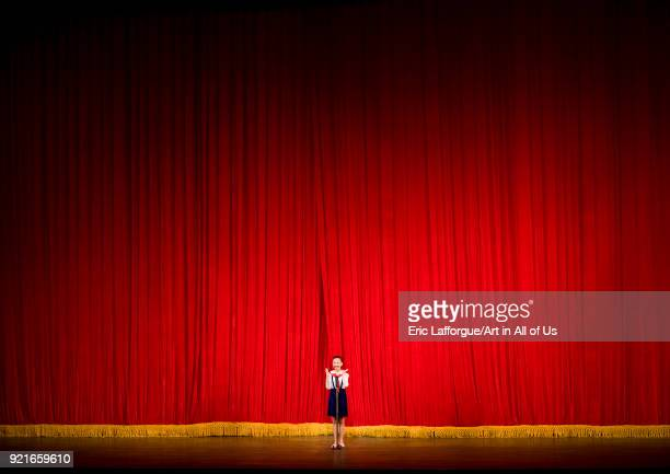 North Korean girl in front of a red curtain on the stage of Mangyongdae theatre Pyongan Province Pyongyang North Korea on April 17 2008 in Pyongyang...