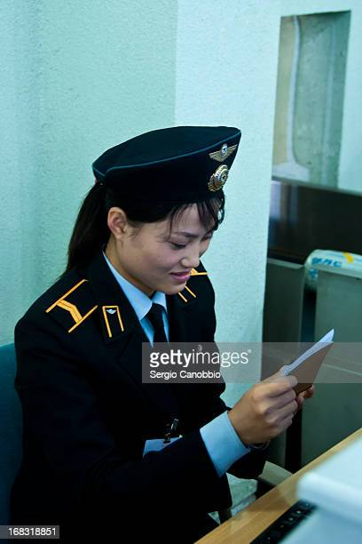North Korean girl performs immigration controls at the airport of Pyongyang, DPRK. Despite the isolationism of the Country, people are quite...