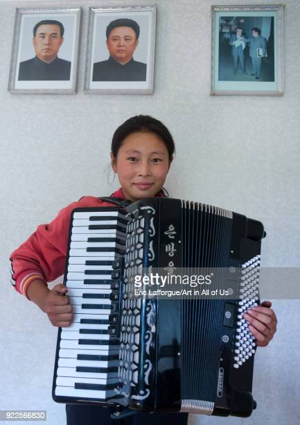 North Korean girl playing accordion under the Dear Leaders portaits South Pyongan Province Chonsam Cooperative Farm North Korea on September 12 2011...