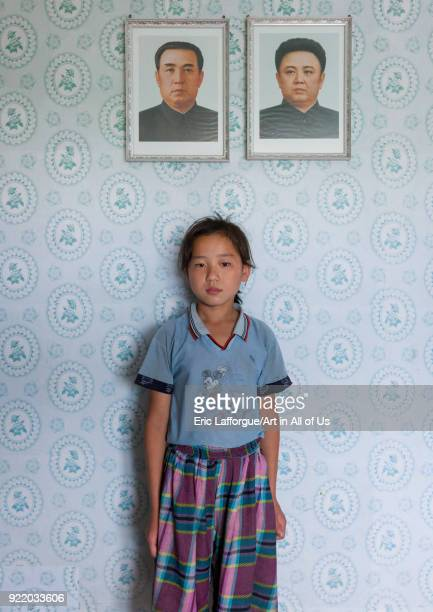 North Korean girl posing below the portraits of the Dear Leaders inside her home Kangwon Province Chonsam Cooperative Farm North Korea on September...