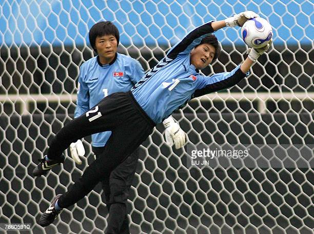 North Korean goalkeeper Jon Myong Hui catches the ball as her teammate Phi Un Hui looks on during a training session in Chengdu in China's...