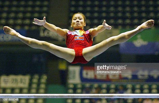 North Korean Han JongOk performs on the uneven bars during the women's apparatus finals for the 14th Asian Games in Busan 04 October 2002 Han won...