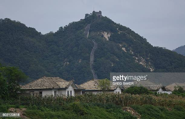 North Korean houses are seen on an island in the Yalu river in front of the Hushan section of the Great Wall of China seen across the border behind...