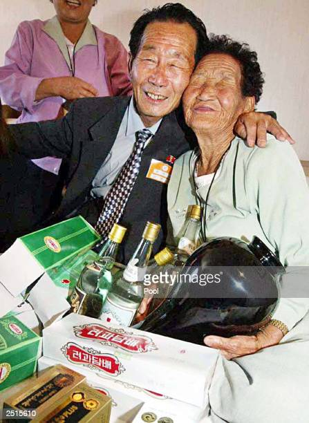 North Korean Jang IkSung smiles with his South Korean sister Jang IkSoon as they give and receive presents during a family reunion at a resort...