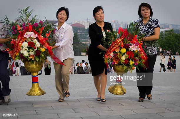 CONTENT] North Korean ladies carrying flower to their leaders statue on the National Day of North Korea