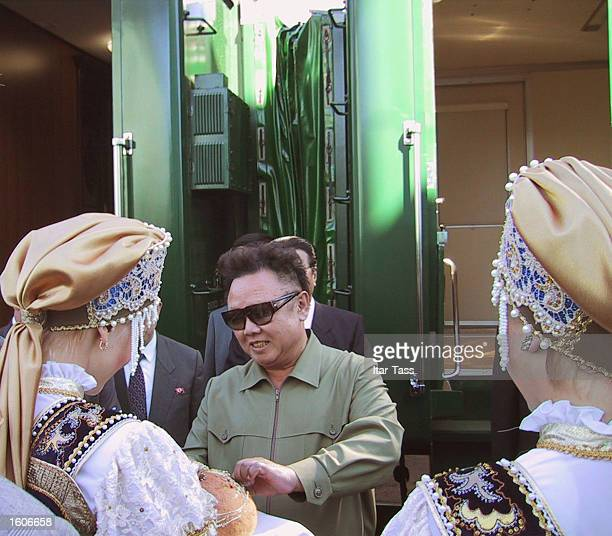 North Korean leader Kim Jong Il, center, is greeted by women in traditional costume as he arrives August 1, 2001 at the train station in the Siberian...
