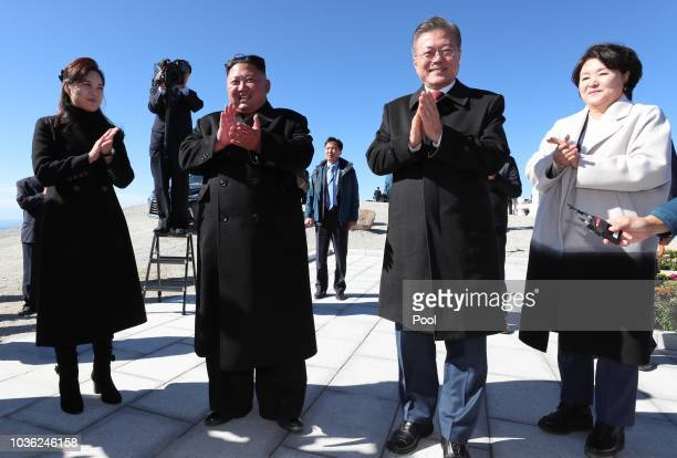 North Korean leader Kim Jong Un and his wife Ri Sol Ju applaud with South Korean President Moon Jaein and his wife Kim Jungsook as they arrive at the...