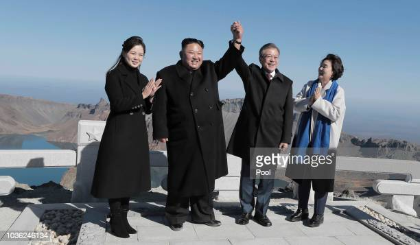 North Korean leader Kim Jong Un and his wife Ri Sol Ju pose with South Korean President Moon Jae-in and his wife Kim Jung-sook on the top of Mount...