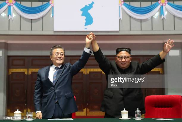 North Korean leader Kim Jong Un and South Korean President Moon Jaein gesture as they watch the gymnastic and artistic performance at the May Day...