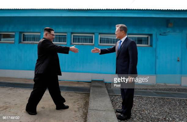 North Korean Leader Kim Jong Un and South Korean President Moon Jae-in shake hands over the military demarcation line upon meeting for the...