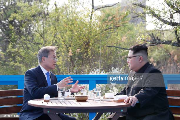 North Korean leader Kim Jong Un and South Korean President Moon Jaein talk in private during the InterKorean Summit on April 27 2018 in Panmunjom...