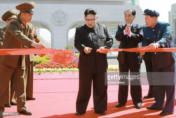 North Korean leader Kim Jong Un cuts the tape at the opening ceremony for a newly constructed residential area on Ryomyong Street in Pyongyang on...