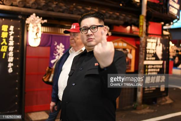 North Korean leader Kim Jong Un impersonator gives the finger as he walks in a street of Osaka during the G20 Osaka Summit on June 28, 2019.