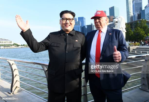 North Korean leader Kim Jong Un impersonator Howard X and Donald Trump impersonator Dennis Alan stand along the Merlion park in Singapore on June 8...