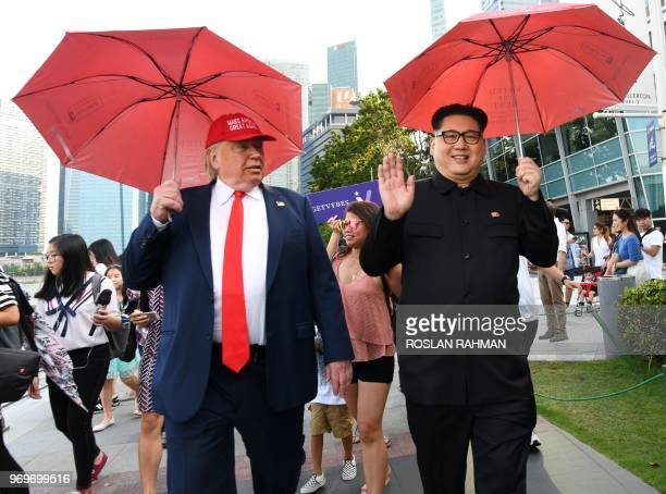 North Korean leader Kim Jong Un impersonator Howard X and Donald Trump impersonator Dennis Alan walk along the Merlion park in Singapore on June 8...