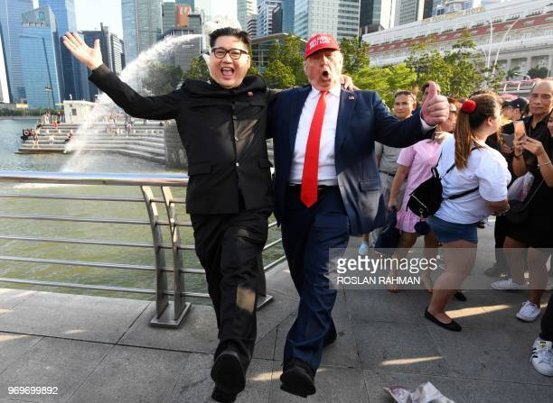 North Korean leader Kim Jong Un impersonator Howard X and Donald Trump impersonator Dennis Alan react at the Merlion park in Singapore on June 8 2018
