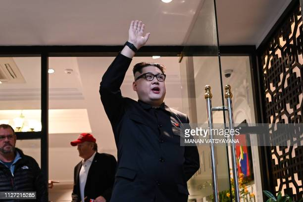 North Korean leader Kim Jong Un impersonator Howard X waves as he is being escorted by Vietnamese authorities to the airport for deportation in Hanoi...