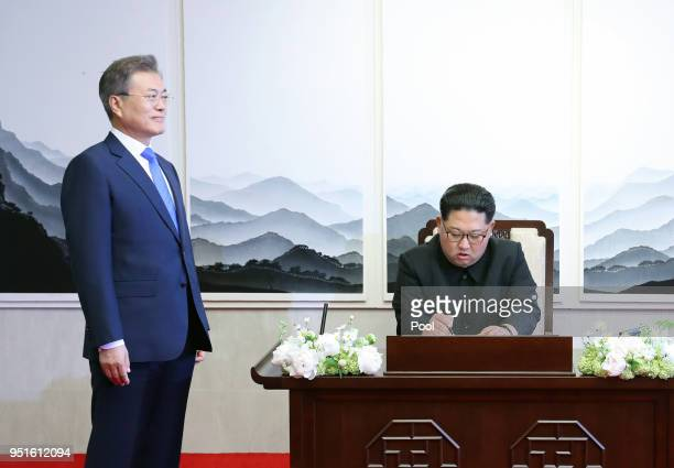 North Korean leader Kim Jong Un signs the guest book as South Korean President Moon Jaein looks on in the Peace House for the InterKorean Summit on...