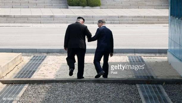 North Korean leader Kim Jong Un takes hand of South Korean President Moon Jaein to cross the military demarcation line to the north side upon meeting...