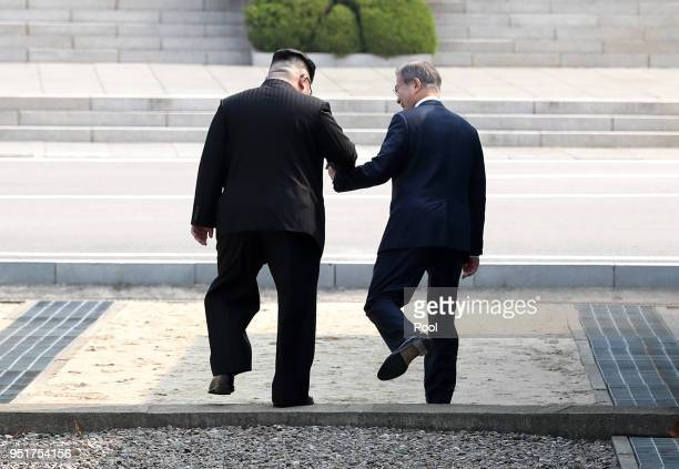 North Korean leader Kim Jong Un takes hand of South Korean President Moon Jae-in to cross the military demarcation line to the north side upon...