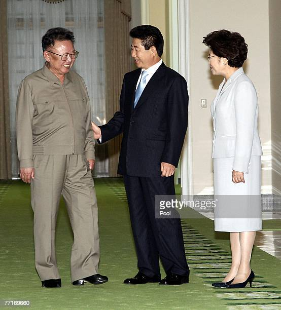 North Korean leader Kim JongIl listens to South Korean President Roh MooHyun while his wife Kwon YangSook looks on before their meeting on October 3...