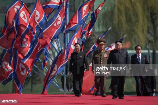 North Korean leader Kim JongUn arrives flanked by vicechairman of the State Affairs Commission Choe YongHae and prime minister Pak PongJu at an...