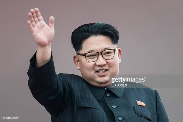 North Korean leader Kim JongUn waves from a balcony of the Grand People's Study House following a mass parade marking the end of the 7th Workers...