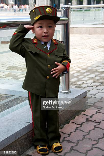 North Korean little boy in army uniform salutes for the tourists In Sungristreet Pyongyang