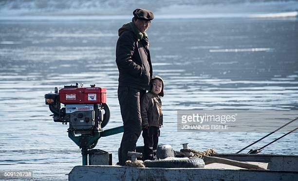 A North Korean man and his son stands on a boat on of the Yalu River at the town of Sinuiju across from the Chinese border town of Dandong on...