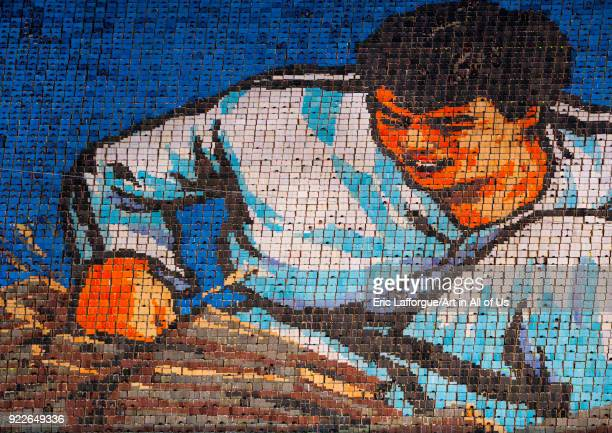 North Korean man breaking a brick made by children pixels holding up colored boards during Arirang mass games in may day stadium Pyongan Province...