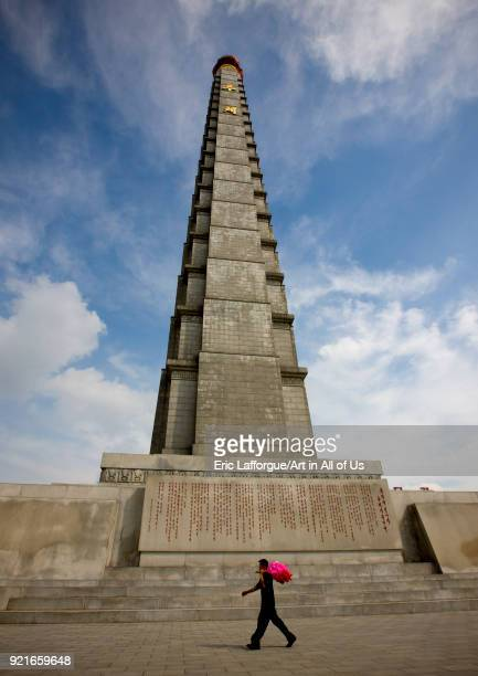 North Korean man going to a parade with flowers passing in front of Juche tower Pyongan Province Pyongyang North Korea on September 9 2008 in...